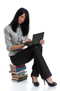 woman sitting on books with a laptop