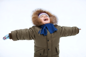 child in a snow suit happy