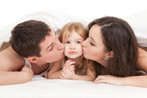 parents kissing kid