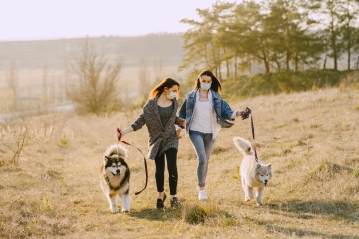 Canva - Female friends in face masks walking with dogs in countryside